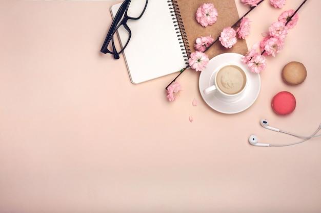 Copo branco com cappuccino, flores de sakura, macarons, notebook