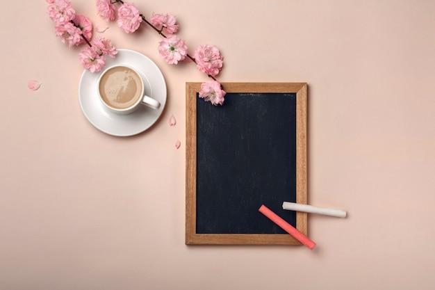 Copo branco com cappuccino, flores de sakura, quadro de giz sobre um fundo rosa pastel.