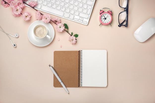 Copo branco com cappuccino, flores de sakura, teclado, despertador, notebook em um fundo rosa pastel