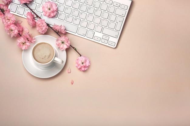 Copo branco com cappuccino, flores de sakura, teclado em um fundo rosa pastel