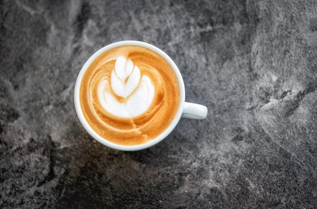 Copo branco com cappuccino fresco com um belo padrão na espuma em uma mesa de textura escura. ficus macio.