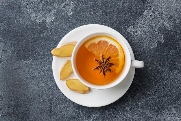 Copo branco com chá de ervas natural com canela e limão.