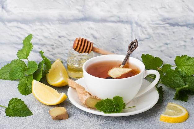 Copo branco com chá de ervas natural, gengibre, hortelã e mel.