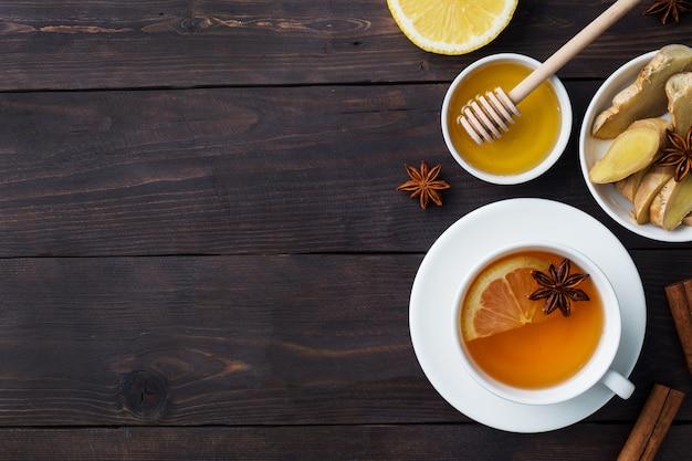 Copo branco com chá de ervas natural, gengibre, limão e mel e canela.