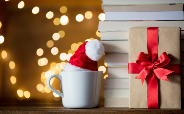 Copo branco com chapéu de natal e livros