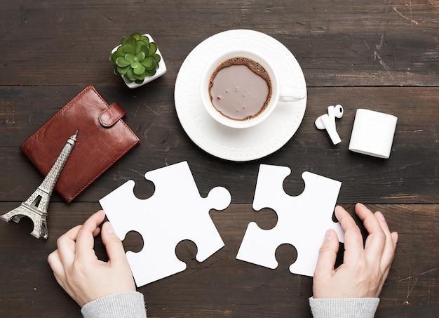 Copo branco com chocolate e duas mãos femininas segurando peças de quebra-cabeça brancas em uma madeira marrom
