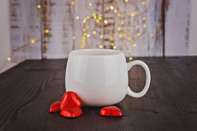 Copo branco com corações vermelhos dos doces de chocolate do valentim