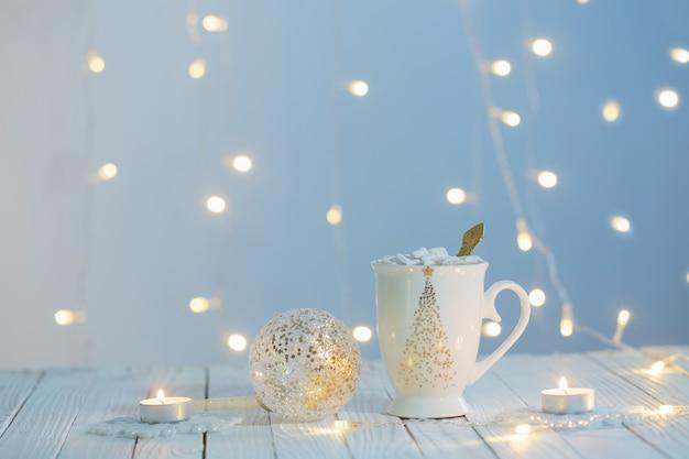 Copo branco com decorações douradas na mesa de madeira branca