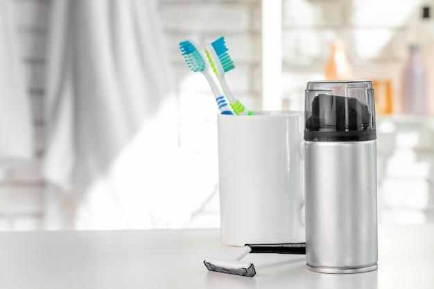 Copo branco com escovas de dentes e toalhas no banheiro