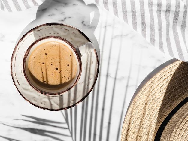 Copo branco com formas vermelhas, cheio de café cremoso em um fundo branco com um pano cinza e branco listrado coberto por uma sombra de folha de ficus e um chapéu