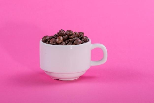 Copo branco com grãos de café em uma parede rosa