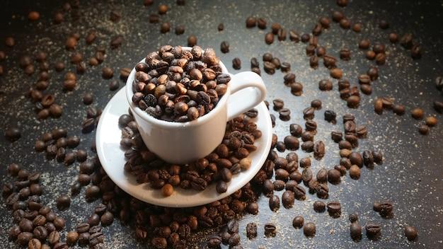 Copo branco com grãos de café sobre fundo preto.