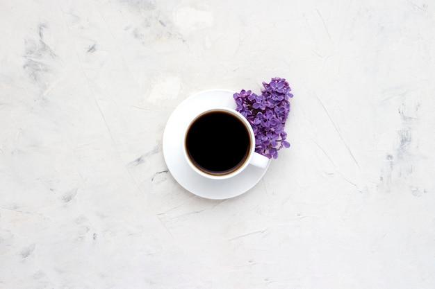 Copo branco com um café e lindas flores lilás em uma superfície branca