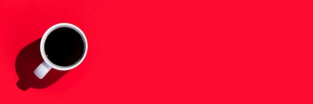 Copo branco com um café em um espaço vermelho isolado. vista superior, configuração plana. bandeira.