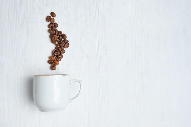 Copo branco com vapor abstrato de grãos de café sobre um fundo branco de madeira.