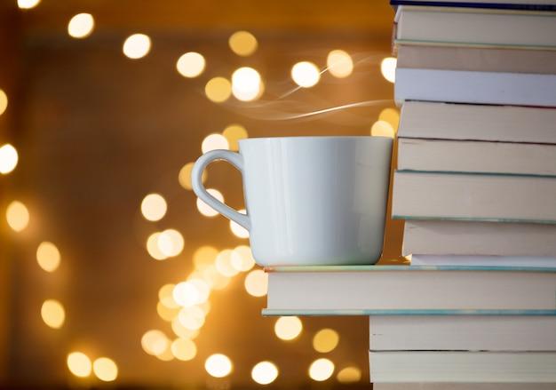 Copo branco de bebida quente perto da pilha de livros e luzes de fada