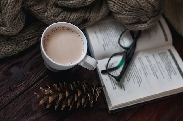 Copo branco de cacau em uma velha mesa de madeira com um livro divertido e óculos de leitura.