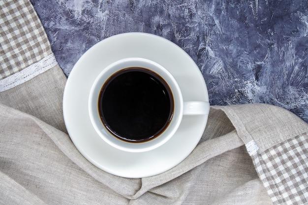 Copo branco de café preto americano e um lindo xale feito de tecido sobre uma mesa cinza. bela composição da taça. camada plana, vista superior, espaço de cópia. conceito de relaxamento.