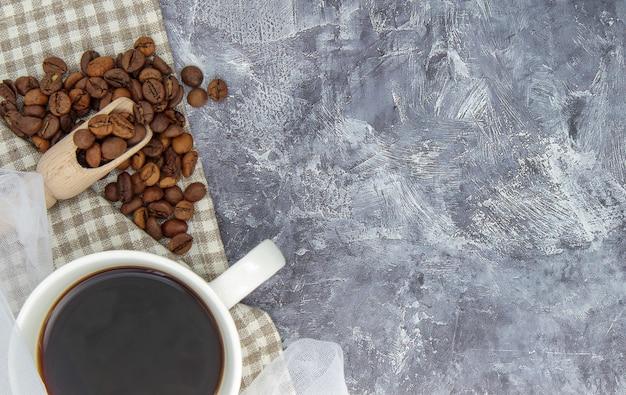 Copo branco de café preto americano, xale de pano com grãos de café espalhados sobre uma mesa cinza. bela composição da taça. camada plana, vista superior, espaço de cópia. conceito de relaxamento.