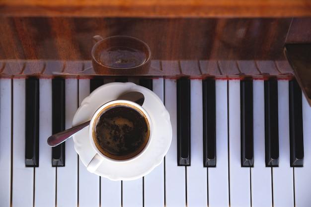 Copo branco de café preto nas teclas de piano retrô