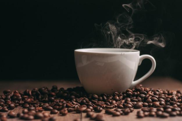 Copo branco de grãos de café torrados e vapor em um fundo escuro
