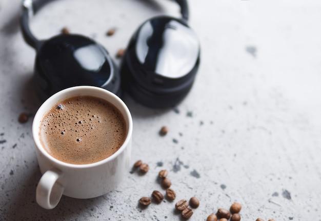 Copo branco do café e fones de ouvido na tabela concreta. audiobook e podcast