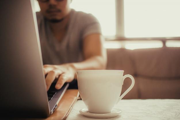 Copo branco do café quente na tabela de um homem autônomo.