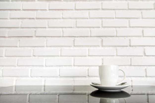 Copo branco do café quente sobre a tabela de vidro com fundo branco da parede de tijolo. conceito fot beber um