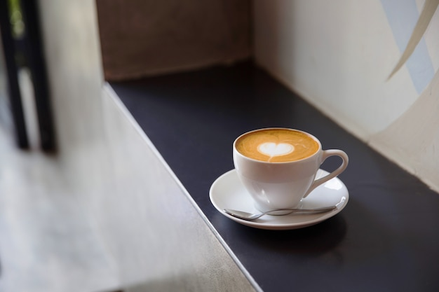 Copo branco do cappucino saboroso com latte da arte do amor.