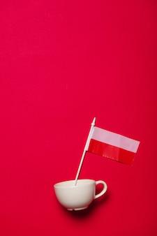 Copo branco e bandeira de poland em fundo vermelho