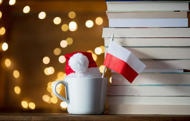 Copo branco e chapéu de natal com bandeira de itália perto de livros
