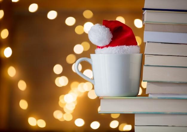 Copo branco e chapéu de natal perto de livros