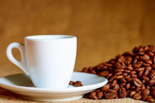 Copo branco e grãos de café na turva.
