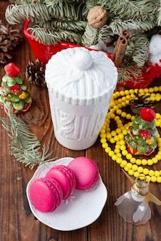 Copo branco e macaroons rosa com decorações de natal em fundo de madeira