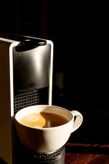 Copo branco em pé na grade da máquina de café com café derramando na xícara no restaurante, cafeteria, bar. coffee break concept.fresh bebida quente no copo branco. copie o espaço