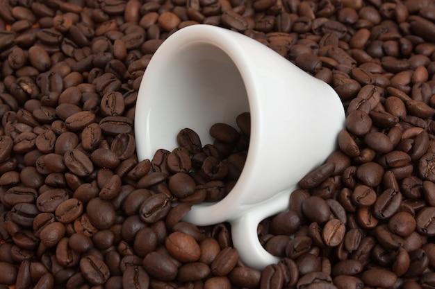 Copo branco em uma pilha de grãos de café