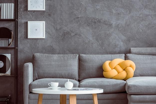 Copo branco na mesa de centro de madeira na sala de estar com almofada amarela no sofá cinza contra a parede de concreto