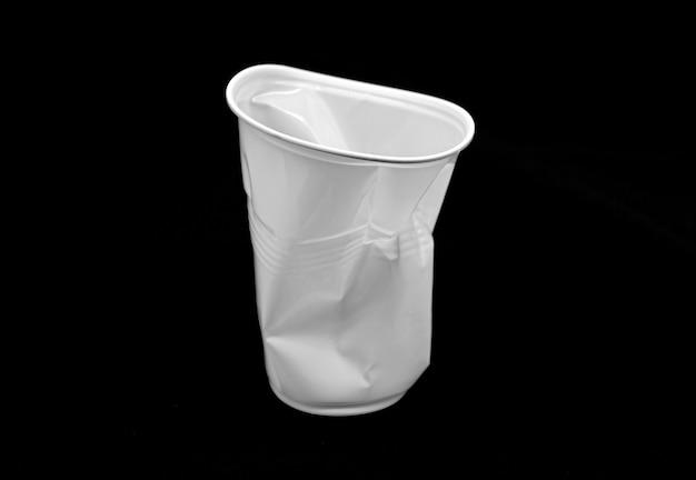 Copo branco plástico amassado isolado