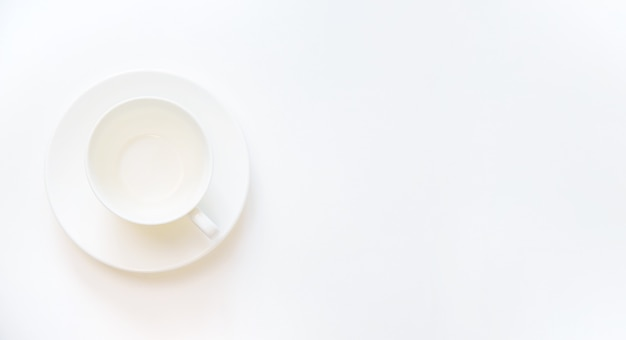 Copo branco vazio sobre um fundo branco. foco seletivo.