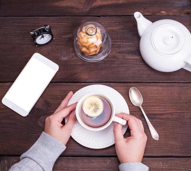Copo cerâmico branco com chá preto e limão