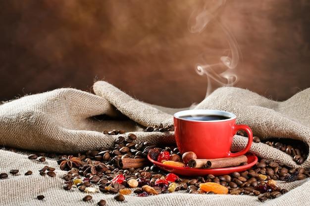 Copo cerâmico vermelho com café quente em placas de madeira.