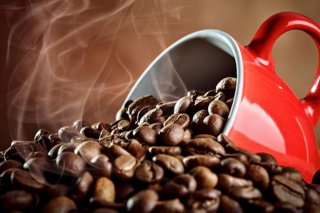 Copo cerâmico vermelho com café quente em tábuas de madeira.