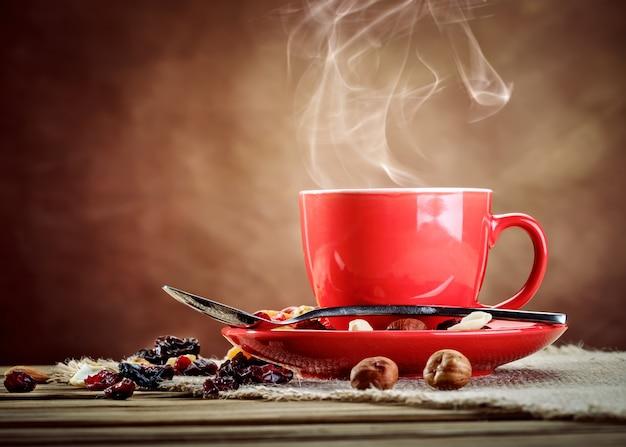 Copo cerâmico vermelho com café quente.