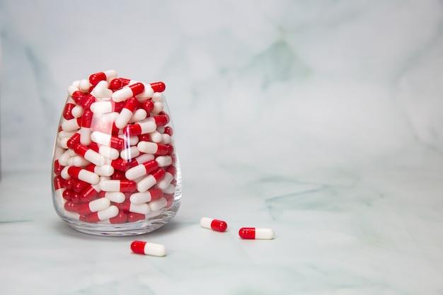 Copo cheio com cápsulas de comprimidos para medicação. medicamentos ou vitaminas, comprimidos de medicamentos farmacêuticos diversos