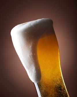 Copo cheio de cerveja em um marrom