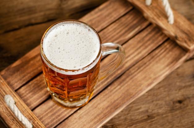 Copo cheio de cerveja lager em fundo rústico de madeira