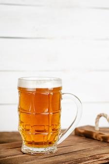 Copo cheio de cerveja loira na parede de madeira branca vertical, cópia espaço