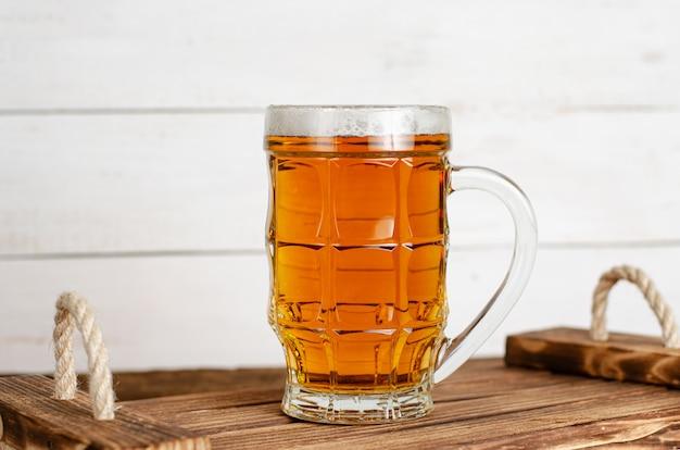 Copo cheio de copo de cerveja na bandeja de madeira rústica.