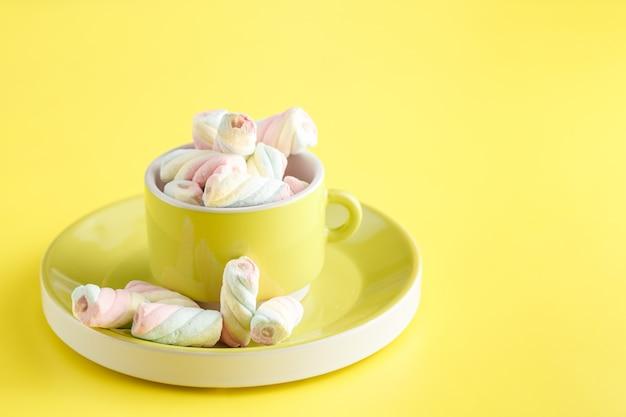 Copo cheio de doce marshmallow torcido em fundo amarelo brilhante