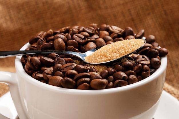 Copo cheio de grãos de café e colher com açúcar mascavo